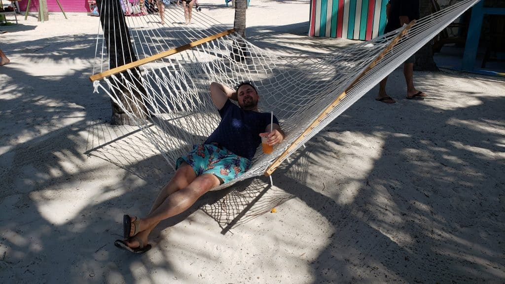 man smiling and laying in hammock on beach