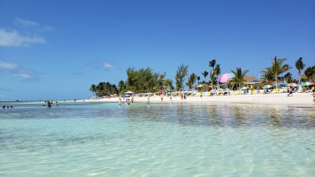 clear ocean water against a beach with colorful umbrellas - cococay island