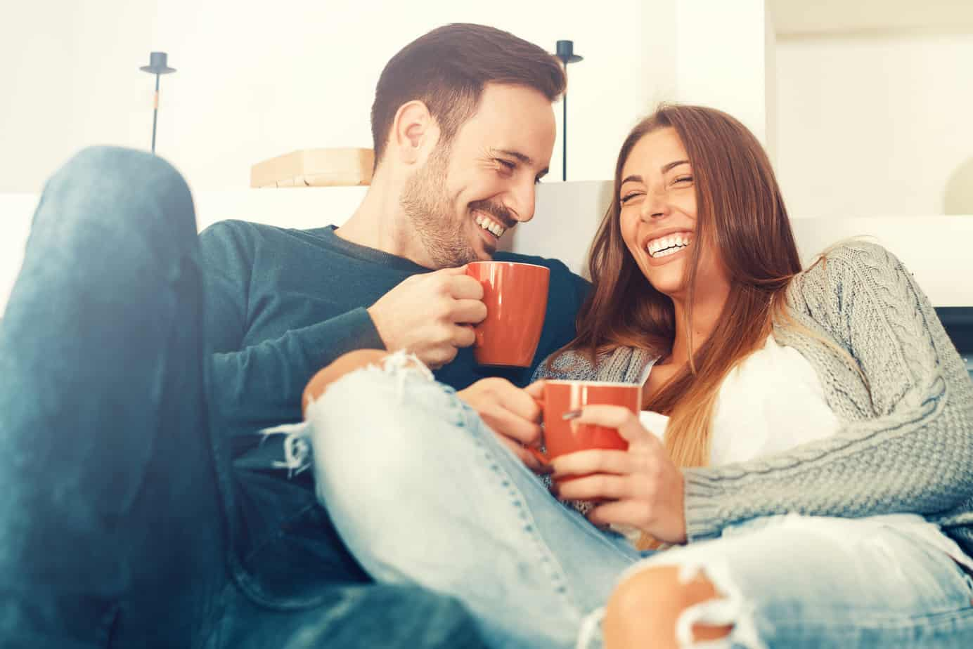 tips for a long distance relationship - couple sitting on couch drinking from red mugs