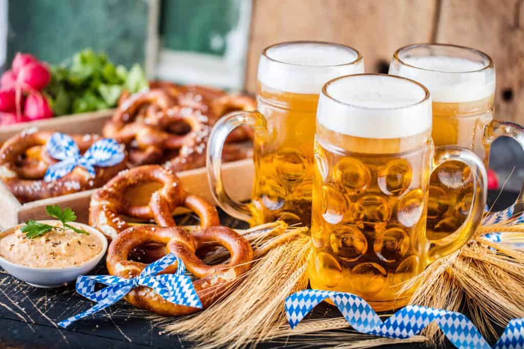 beer in steins with pretzels and blue ribbons
