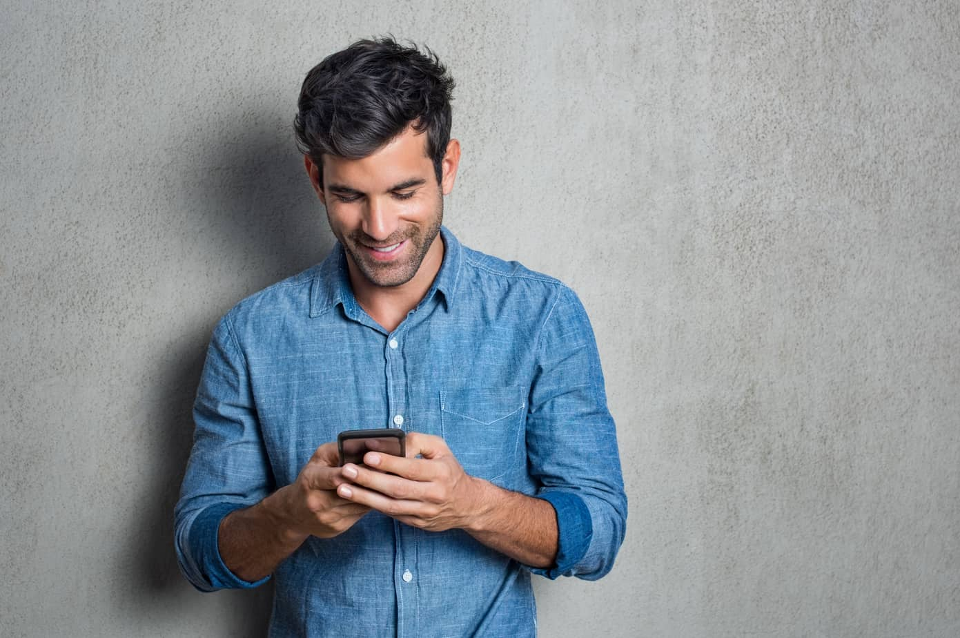 handsome guy smiling at phone - reading flirty texts for him