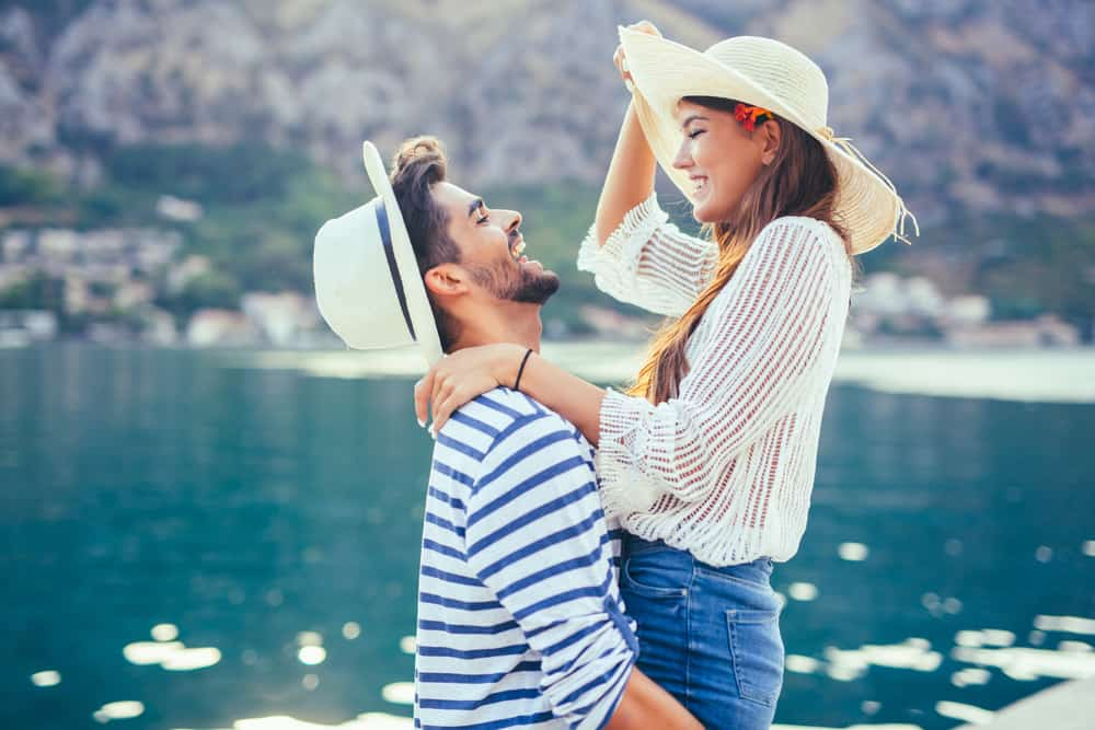 long distance date ideas header - couple in front of mediterranean water smiling and laughing. man is lifting up girl, both are wearing white hats