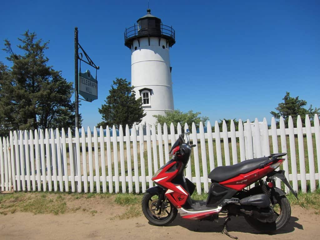 red moped in front of white fence and lighthouse - activities for a romantic getaway cape cod