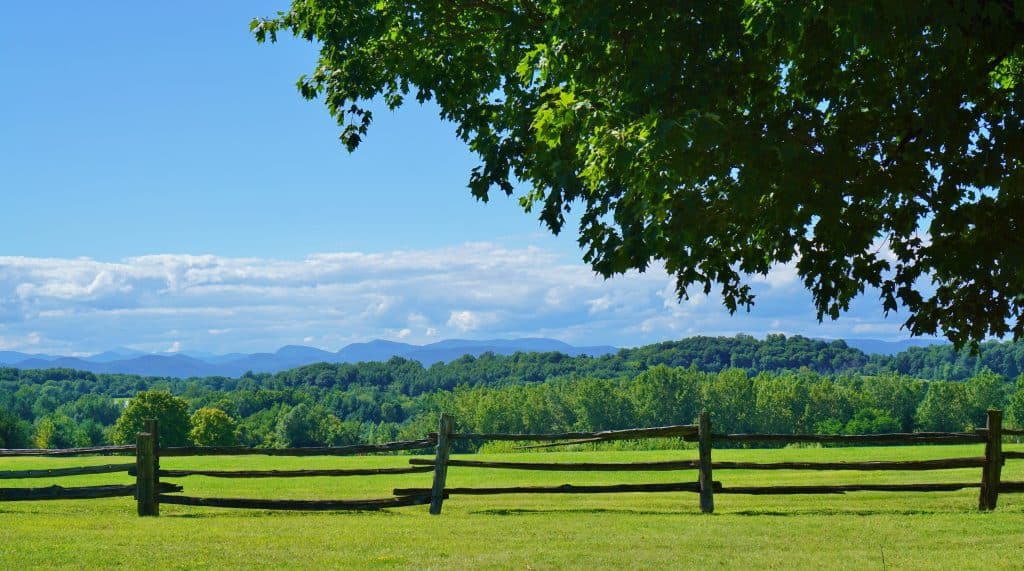 a green field with a wooden fence in front of it, mountains in the distance - burlington vermont points of interest