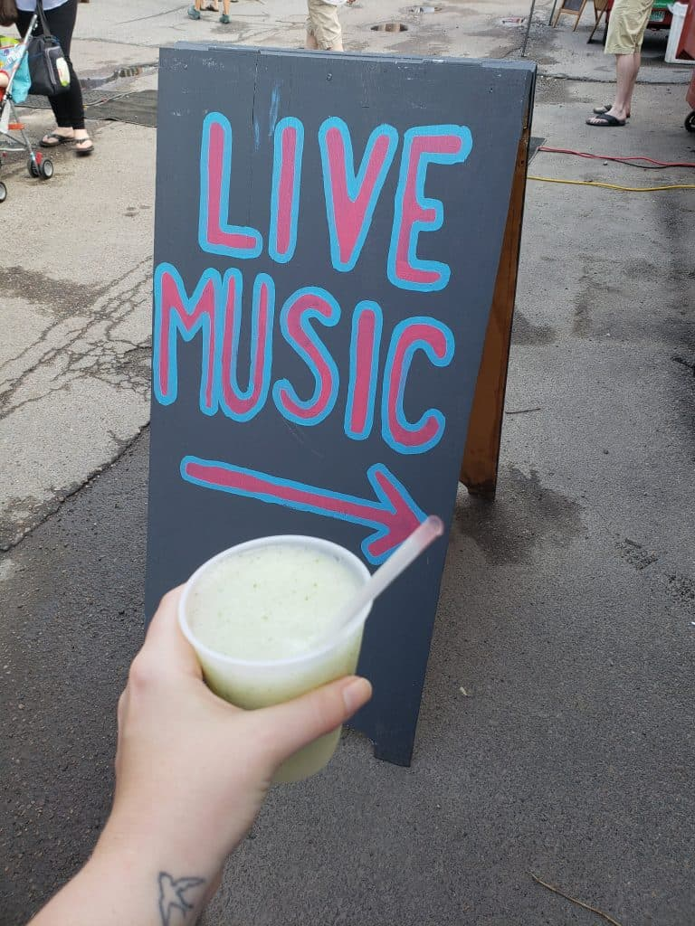 hand holding iced drink in front of sign that reads Live Music - burlington vt tourist attractions
