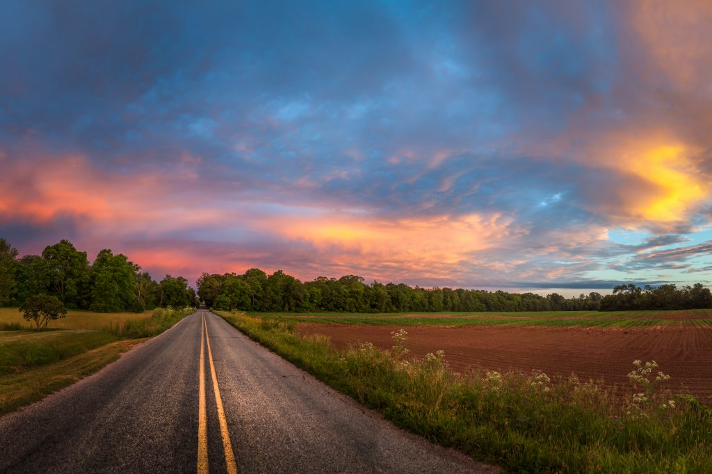 beautiful colorful sunset over flat country road next to field