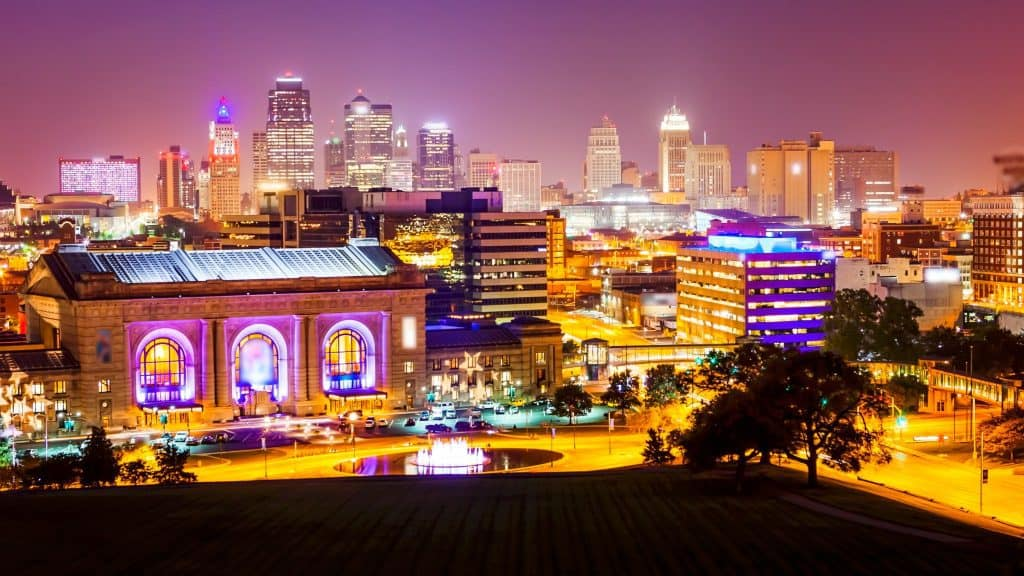 a colorful city skyline at night with lots of neon - Kansas, City, Missouri