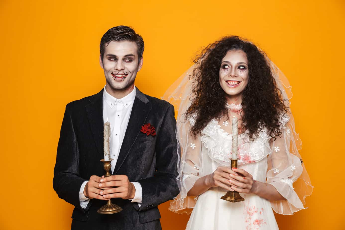 couples halloween costumes header image - photo of spooky bride and groom halloween couple in front of bright orange wall