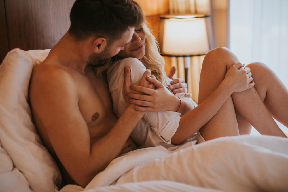 10 rules for a happy marriage header image - couple cuddling on bed with white sheets