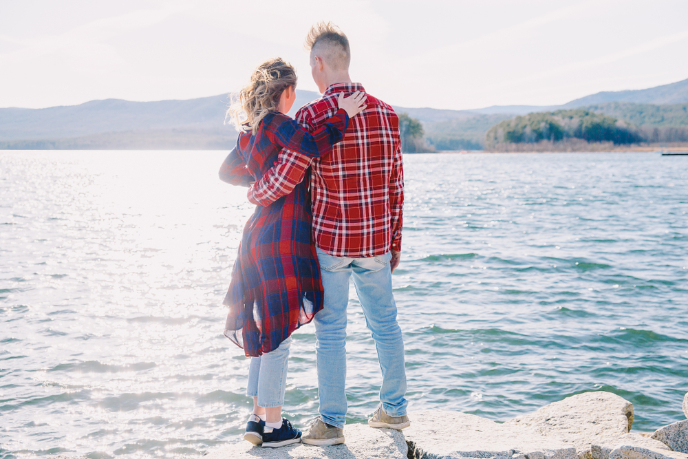 couple standing in front of a lake with their backs to the camera. they have their arms on each other's shoulders. they both wear red and blue plaid shirts