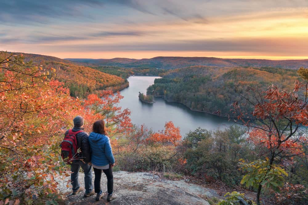 couple standing at a mountain top overlooking a river. fall leaves are on the trees and the sun is setting in the distance