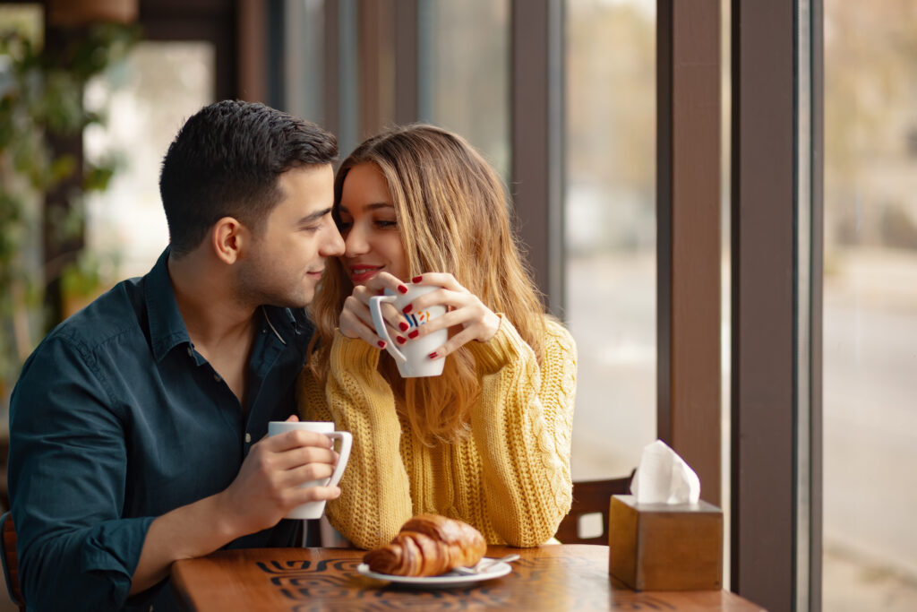 Young attractive couple on date in coffee shop. In love man and woman sitting in a cafe, drinking coffee