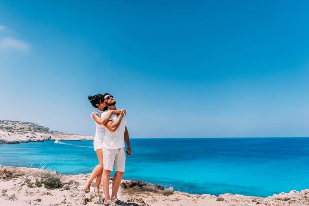 Happy couple by the sea. Man and woman hugging on the beach. Honeymoon lovers. Man and woman on the island. Couple in love on vacation. Sea tour. Honeymoon trip. Couple in love at the blue lagoon