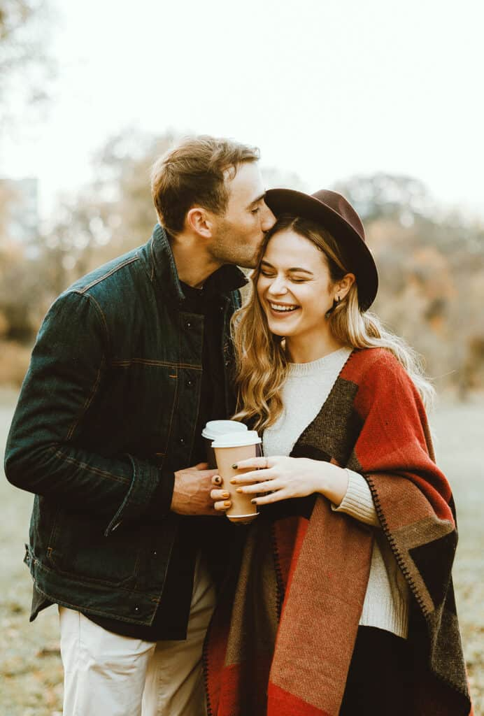 Romantic couple drinking coffee outdoor and smiling - fall season - words of affirmation love language