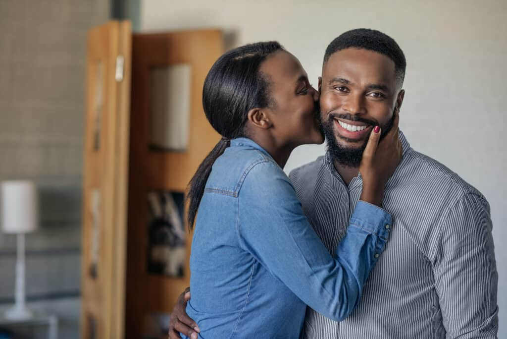 Affectionate African American wife kissing her husband on the cheek