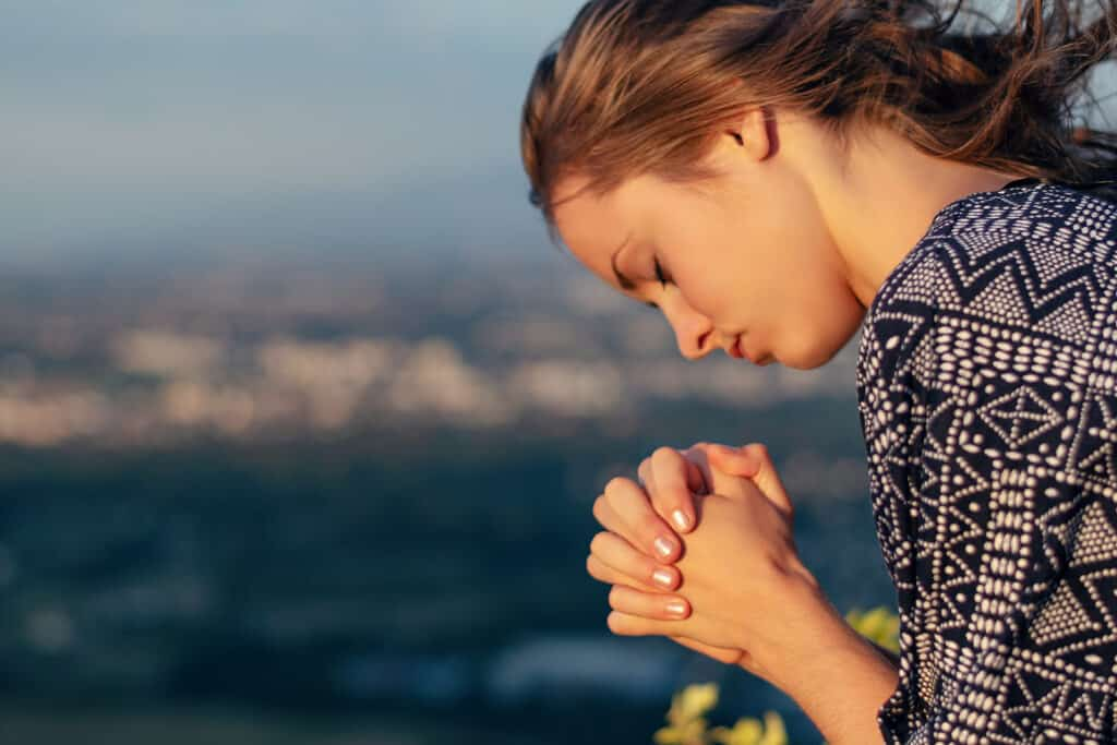 Christian worship and praise. A young woman is praying in the evening.