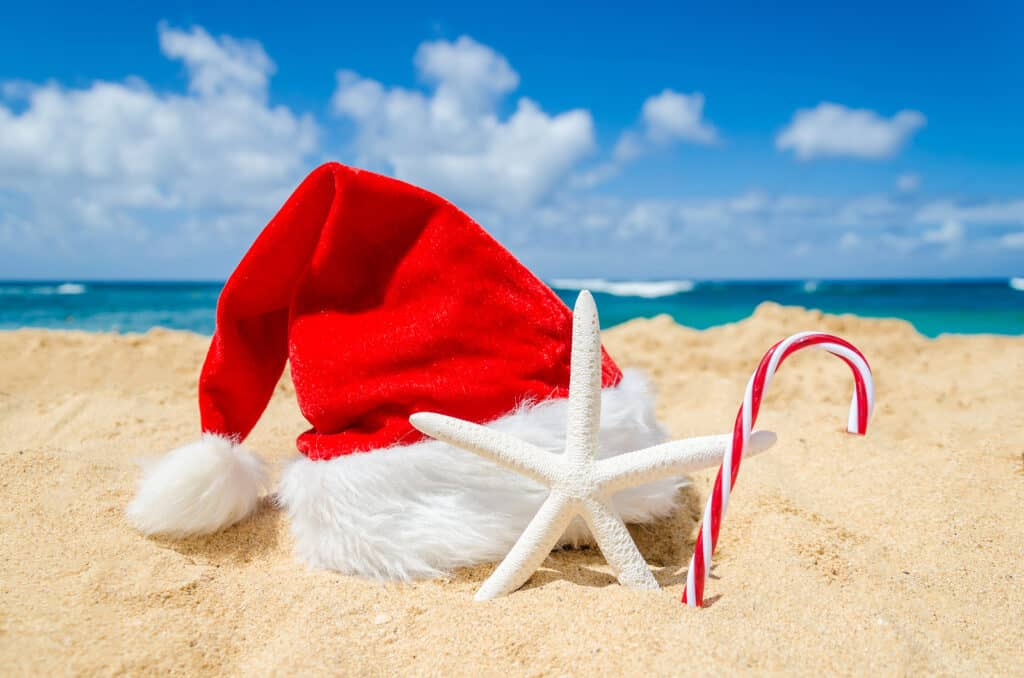 Merry Christmas and Happy New Year background with Santa Claus Hat candy and starfish on the tropical beach near ocean in Hawaii