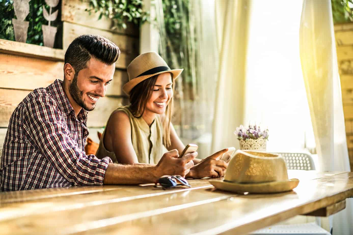photo for budgeting as a couple - couple at table smiling at smartphones