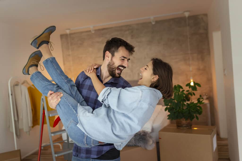 Beautiful newly married young couple moving in together, having fun while unpacking cardboard boxes with their belongings, husband carrying wife in his arms