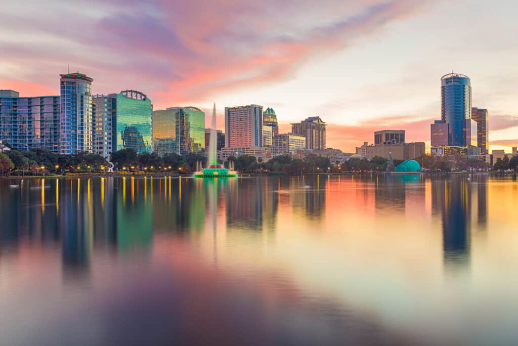 Orlando, Florida, USA downtown city skyline from Eola Park at dusk.
