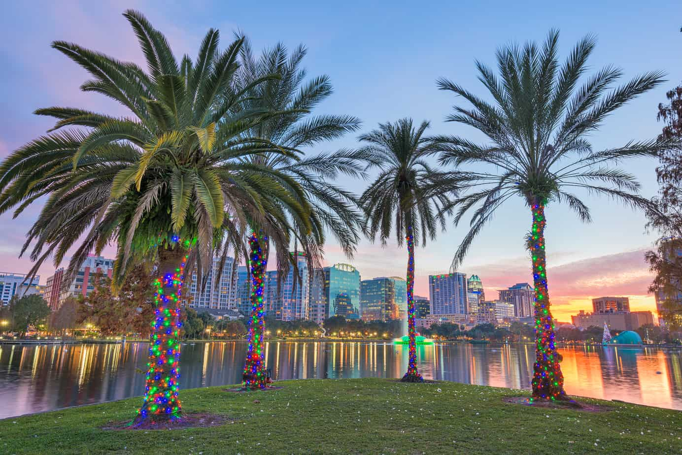 romantic things to do in orlando - Orlando, Florida, USA downtown skyline at Eola Lake at dusk.