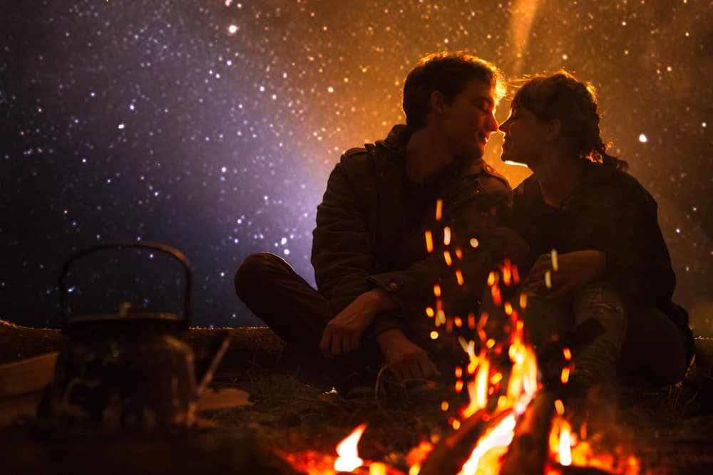 couple sitting in dark outdoor space behind golden campfire