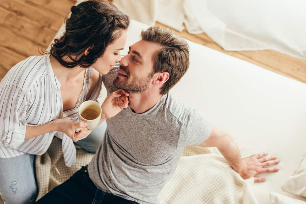 couple enjoying coffee in bed together - a morning coffee ritual can be a great idea for your marriage goals list
