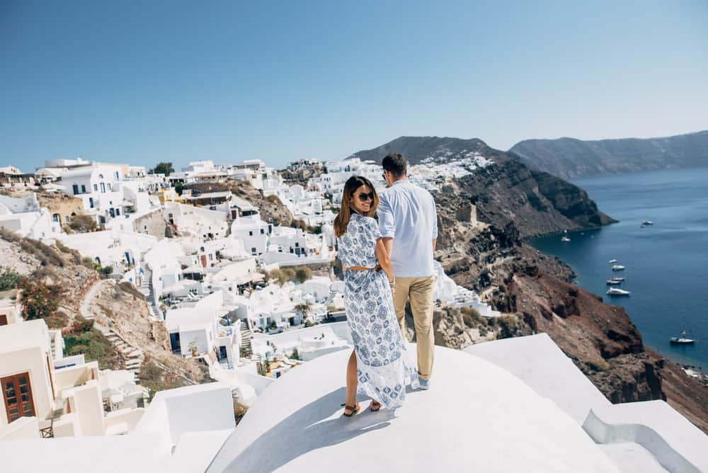 The couple is standing on the roof in Santorini, the girl turned to the camera
