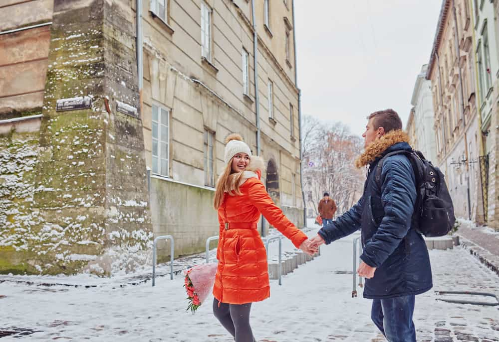 couple holding hands and walking down a snowy street european style architecture