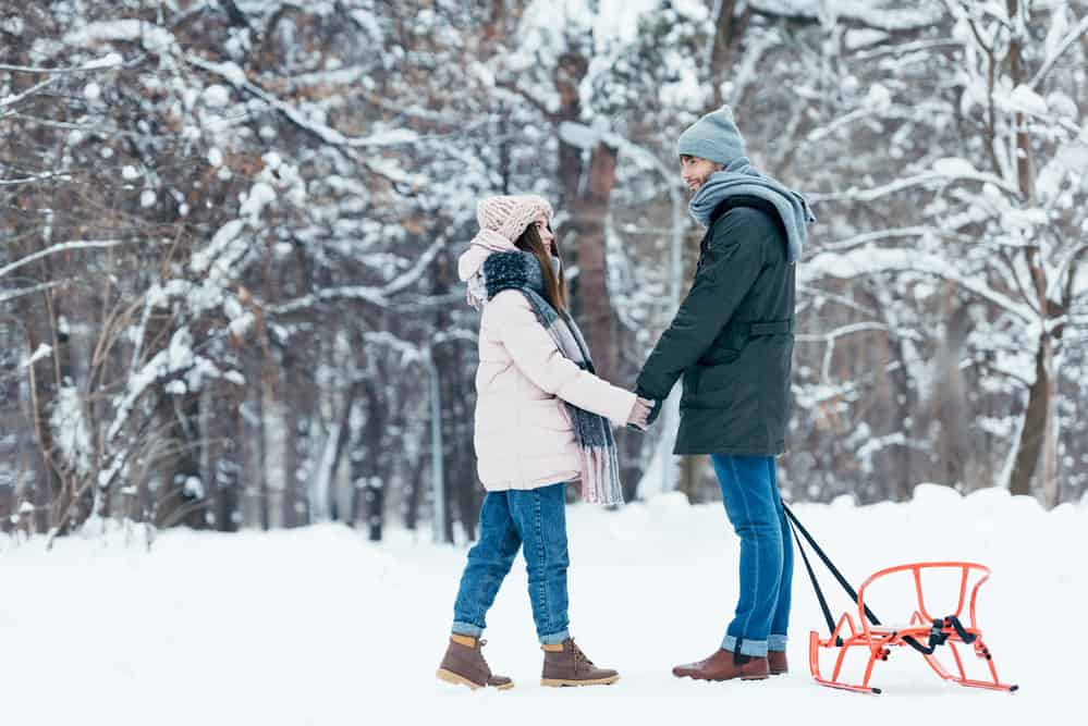 man and woman holding hands standing in the snow with a sleigh - checking an item off their winter bucket list for couples