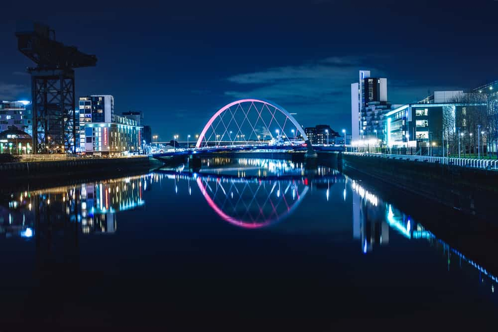 Night view of the Clyde Arc or Squinty Bridge from the East and river Clyde, Glasgow, Scotland - perfect view for romantic glasgow getaway