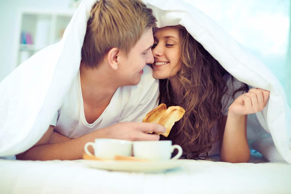 couple under sheets in bed eating toast together with coffee smiling