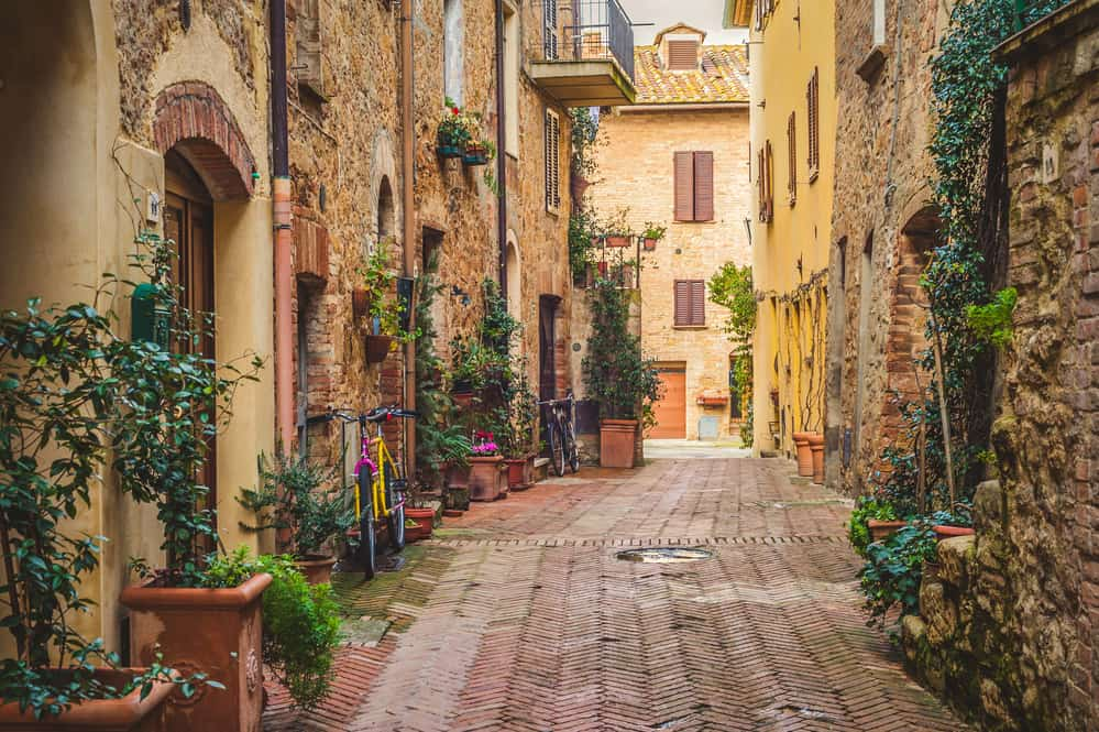 exploring a medieval tuscan town - cobblestone alley with flowers in windows