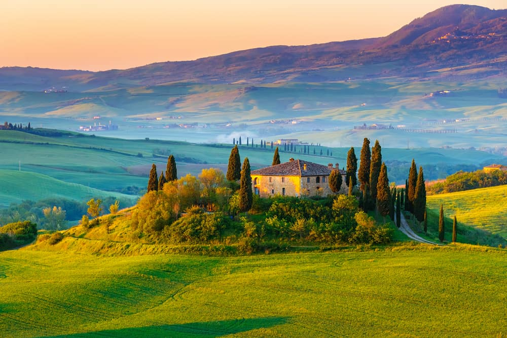 stunning landscape of tuscany - classic italian home surrounded by trees with hills in thre distance - romantic things to do in tuscany