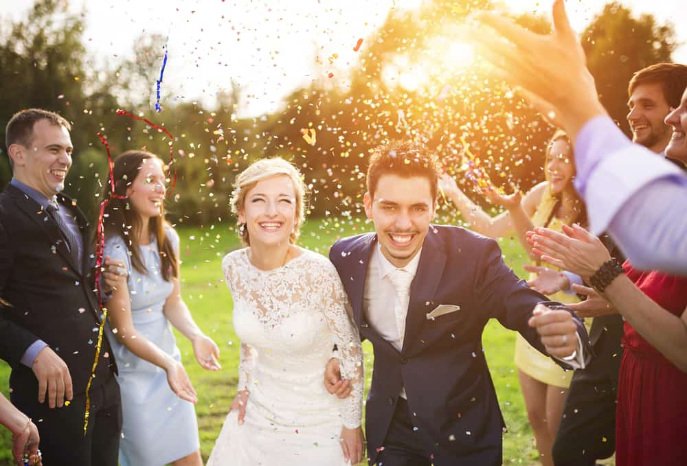 bride and groom surrounded by friends tossing rice, they are smiling and running - instagram captions for weddings