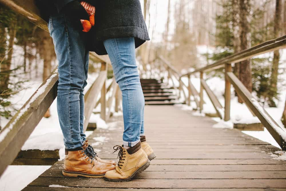 Man kissing young woman standing on toes outdoors in winter park