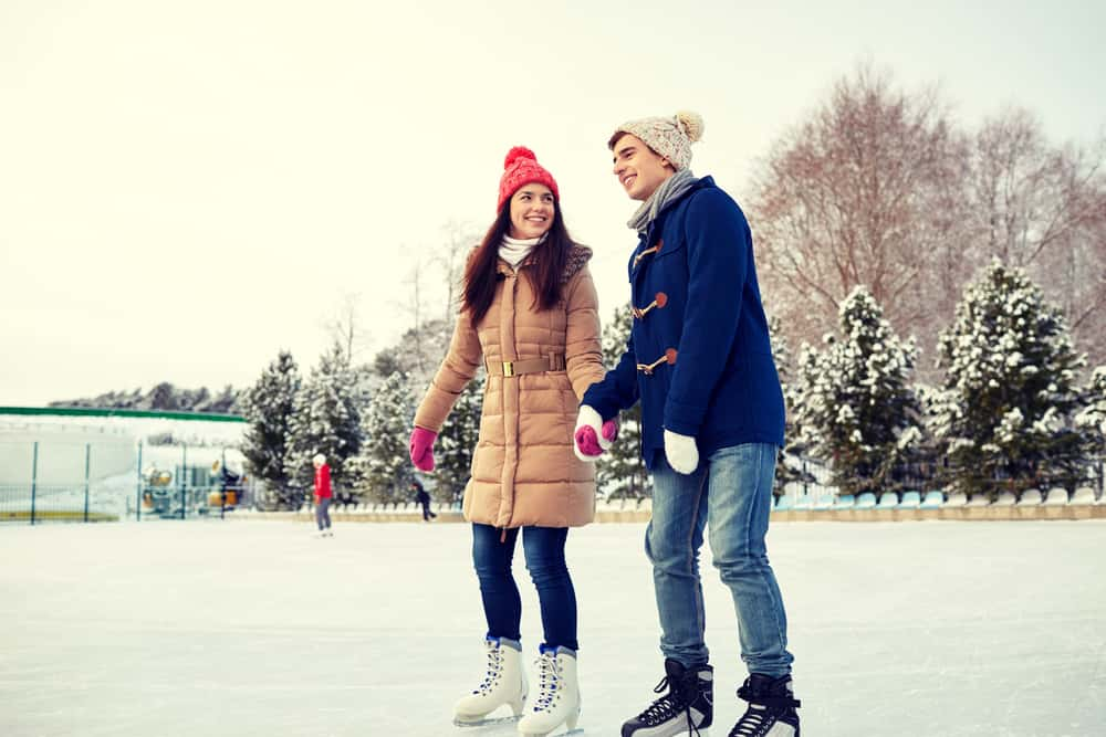 couple holding hands and ice skating on an outdoor pond in winter