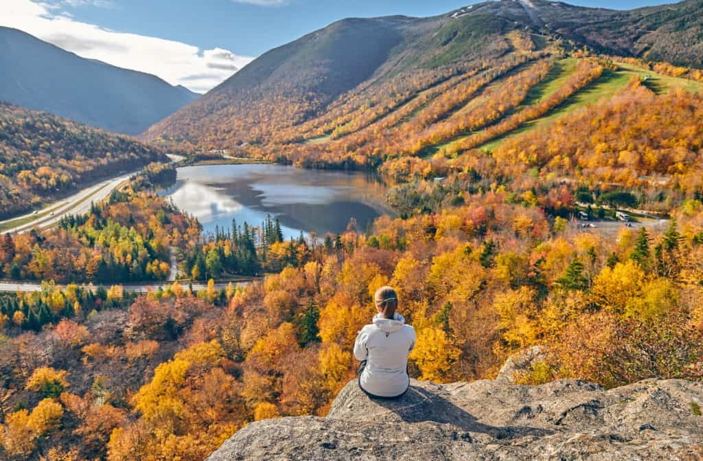 woman sitting on mountain top overlooking lake with fall colored mountains surrounding it