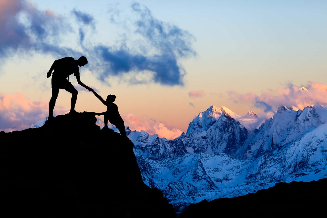 instagram captions for travel- inspiring image of couple silhouetted against tall snowy mountain backdrop, helping one another climb up
