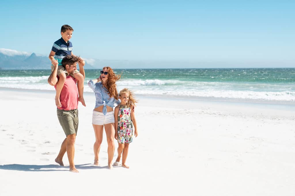 Smiling parents with children at sea. Cute son sitting on father shoulder with mother and sister walking while talking. Happy family with two children enjoying summer holiday at beach with copy space.