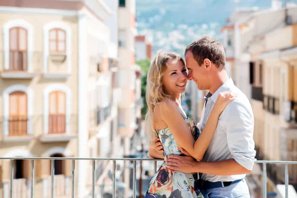 Couple walking in The city of Denia, Spain. Young happy couple smiling and holding each other hand in a summer day. Young man and woman in dress on vacations - couples travel bucket list