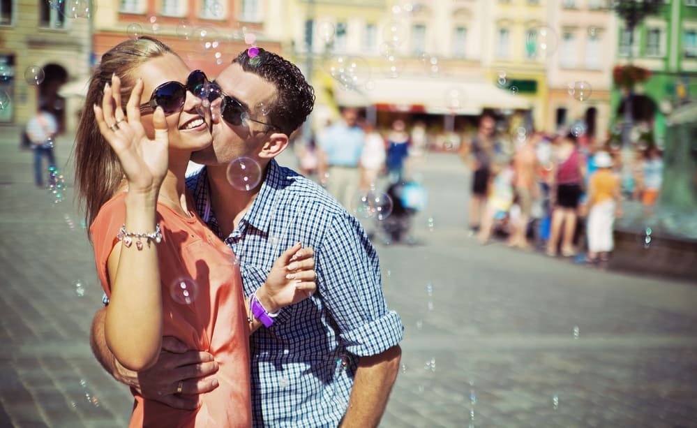 spring bucket list ideas - blowing bubbles together outside - image of couple blowing bubbles in crowded city center