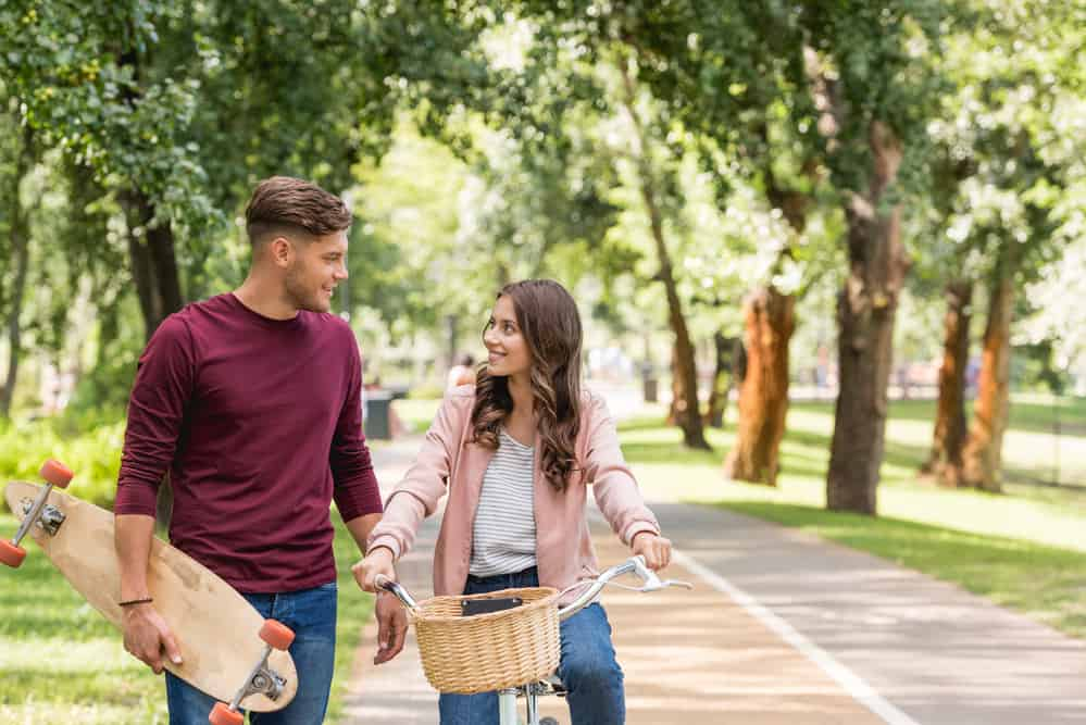 spring date ideas - image of girl on bike and guy standing next to her holding skateboard