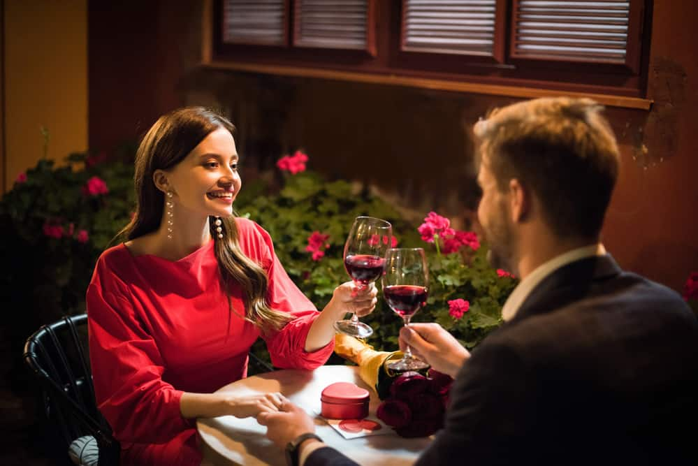 romantic things to do in rhode island header image - couple dining at restaurant with red flowers next to them