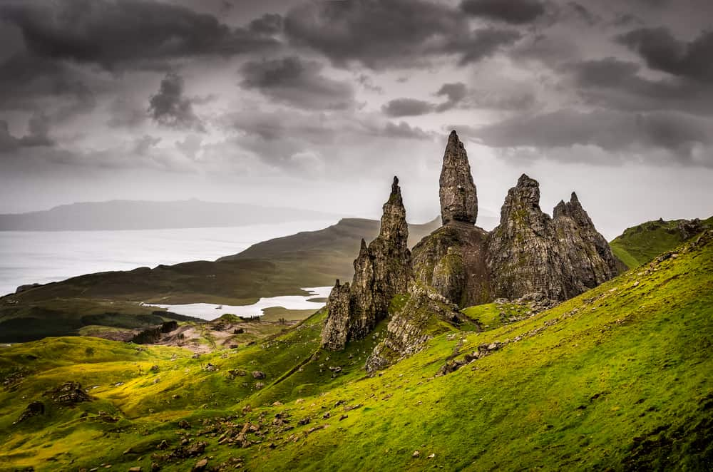 rocky formations on a green hillside, gray cloudy sky above - scottish highlands