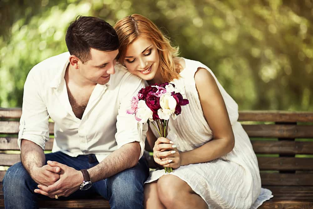 Young attractive couple sitting on bench in the park and romantic smiling.