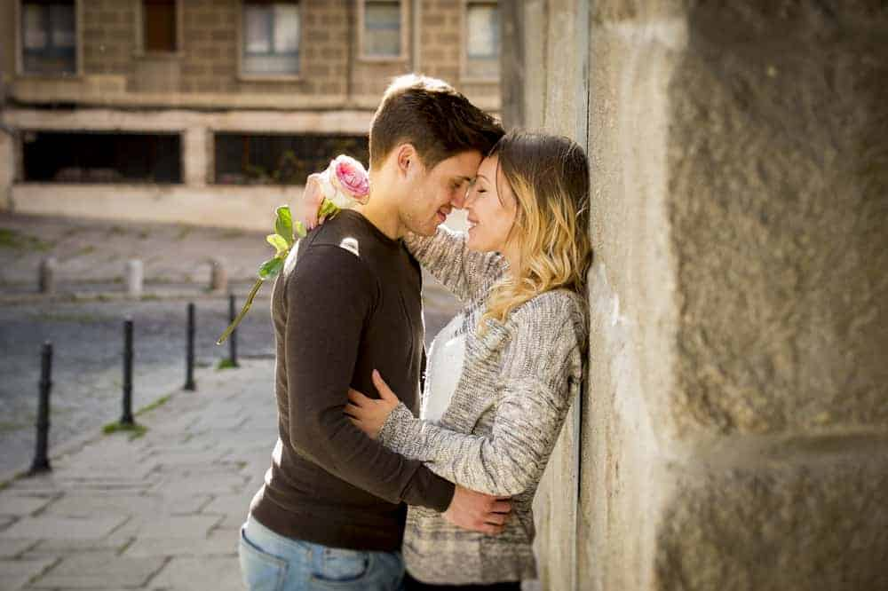 romantic date ideas header image - candid portrait of beautiful European couple with rose in love kissing on street alley celebrating Valentines day with passion against stone wall on urban background