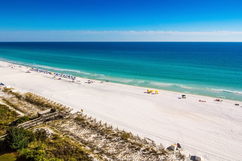 Destin, Florida - Oct. 24, 2014: Beach goers enjoy the white sandy beaches and emerald blue waters of the panhandle in Destin, Florida. Originating as a small fishing village, it is now a popular tourist destination.