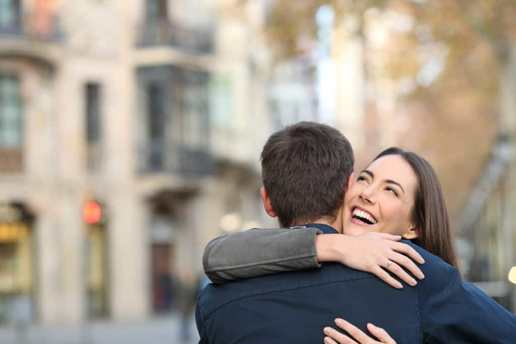 the best quotes about a relationship - header image - couple hugging on city street