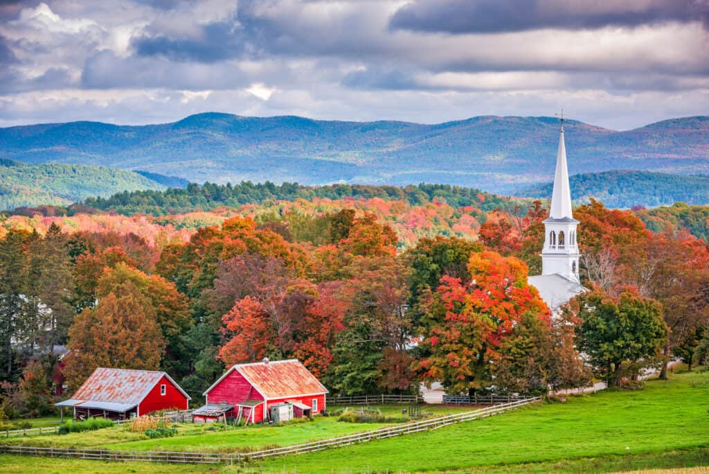 fall is the perfect time for romantic getaways in vermont - image of fall foliage covered mountains behind red barn and white church steeple, classic pastoral shot